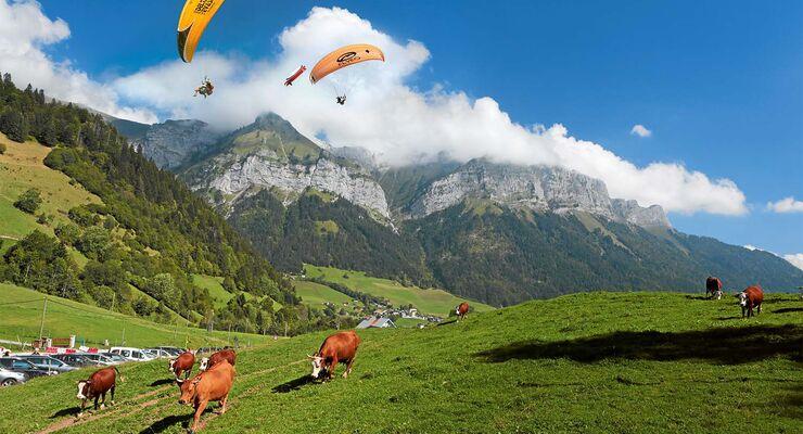 Gleitschirmflieger am Bergmassiv La Tournette über dem Col de la Forclaz