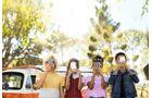 Vier junge Erwachsene stehen mit dem Smartphone vor dem Gesicht da